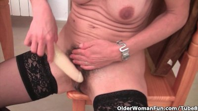 Granny in ebony stockings masturbates her hairy pussy with dildo