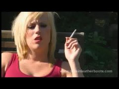 Filthy blonde smoking in knee high leather boots