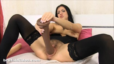 Brunette in stockings with a hairy pussy fucking a massive brutal dildo