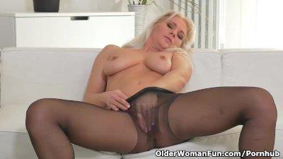 Blonde milf Kathy peels off her black nylons and plays
