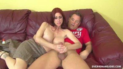 Busty redhead jerks off a boner